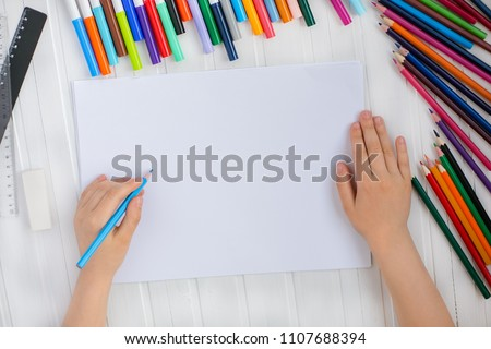 The child's hands are painted with colored pencils on a white sheet of paper on a wooden table. #1107688394
