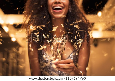Cheerful young woman holding single sparkler in hand outdoor. Detail of african girl celebrating new year's eve with bengal light. Closeup of beautiful woman holding a sparkling stick at party night. #1107694760