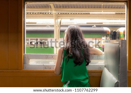 A beautiful charming asian girl in casual dress head out from vintage train window on seat.Feeling look happy and relax on the train. concept.Gorgeous woman sit beside widow. Portrait lady on travel. #1107762299