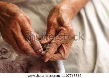 The hand of an old lady was molding a dough made of flour. #1107763562