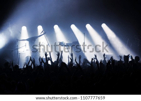 rock band on stage in rays of spotlights in front of crowd of fans with their hands up #1107777659