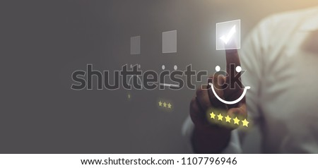 Businessman pressing smiley face emoticon on virtual touch screen. Customer service evaluation concept. Royalty-Free Stock Photo #1107796946