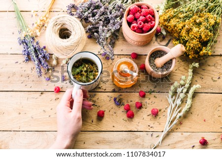 Mug with herbal decoction in the hand of a woman, Collection of medicinal herbs Wild herbs Treatment Wooden background Vintage Rural style, raspberry, honey #1107834017