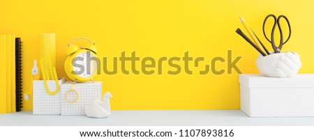 Desk and school supplies over the yellow pastel background. Education, studing and back to school concept Creative desk with yellow wall and stationery. #1107893816