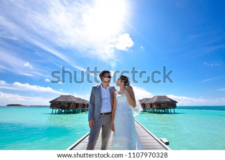 MALDIVES 2014 - Couple is posing and look at each other in front of water villa room in Maldives #1107970328