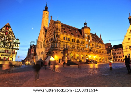 Rothenburg ob der Tauber, Bavaria/ 07/18/2018: Buildings near Rothenburg ob der Tauber's Marketplatz illuminate during blue hour. #1108011614