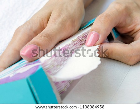 Package of sanitary napkin or sanitary pad in woman's hands for intimate hygiene. Close-up, selective focus.