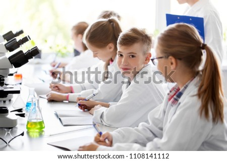 education, science and children concept - teacher and kids studying chemistry at school laboratory and writing to workbooks #1108141112
