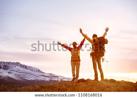 Happy couple with raised arms stands against mountain's sunset sky #1108168016