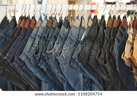 Many jeans hanging on a rack. Row of pants denim jeans hanging in closet. concept of buy , sell , shopping and jeans fashion . #1108204754