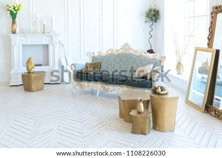 Luxury light interior of living room with gold wall and chic expensive furniture in white and gold colors #1108226030