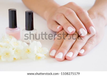 Young, perfect, groomed woman's hands with pink and white nail varnish bottles. Nails care. Manicure, pedicure beauty salon. Beautiful jasmine blossoms on table. Fresh flowers. #1108275179