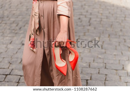 Elegant red high heels shoes in woman hands. Girl wearing beige trench coat standing on a stony pavement, holding her trendy, fashion footwear in hands Royalty-Free Stock Photo #1108287662