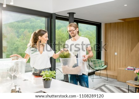 Young and happy couple unpacking different home stuff making order in their new and modern house #1108289120