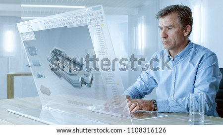 In the Near Future Professional Engineer Works on Transparent Computer Display, Constructing 3D Model of Nextgen Gear Box. He Works in a Bright and Modern Office.