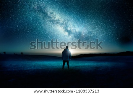 A man stands watching with wonder and amazement as the moon and milky way galaxy fill the night sky. Night time landscape. Photo composite. #1108337213