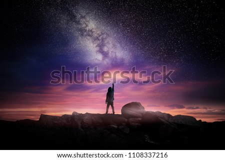 Night time long exposure landscape photography. A man standing in a high place reaching up in wonder to the Milky Way galaxy, photo composite. #1108337216