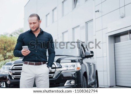 A young, solid businessman and his car near the office. #1108362794