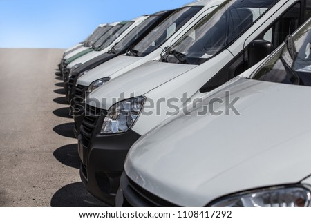 number of new white minibuses and vans outside #1108417292