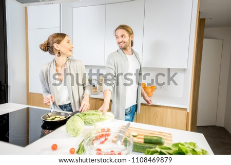 Young cheerful couple dressed alike in gray sweaters cooking some veggie food at the modern kitchen #1108469879
