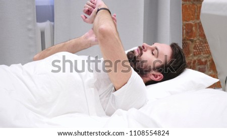 Beard Man Using Smartwatch for Browsing, Email and Messages in Bed #1108554824