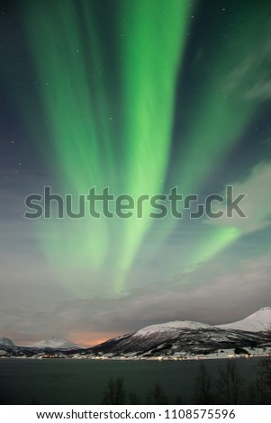 Bright green northern light streaks over Balsfjord, Norway, near Tromso #1108575596