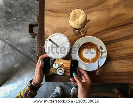 Hand holding cell phone to take photo coffee on the wooden table, top view and blurred background #1108588016
