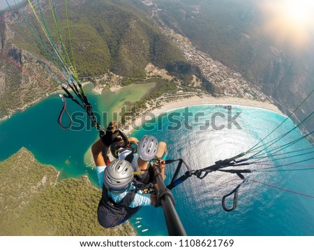 Paragliding in the sky. Paraglider tandem flying over the sea with blue water and mountains in bright sunny day. Aerial view of paraglider and Blue Lagoon in Oludeniz, Turkey. Extreme sport. Landscape #1108621769