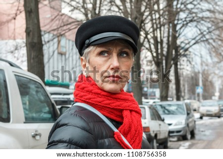 pretty and serious middle-aged lady in a red scarf, cap, earrings and black jacket against the background of the city. closeup portrait of elegant middle aged woman. Lovely middle-aged gray woman #1108756358
