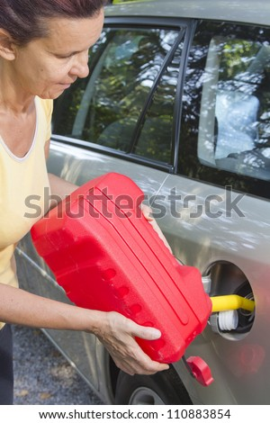 Mid aged woman adding fuel in car with red plastic gas can (fuel container) #110883854