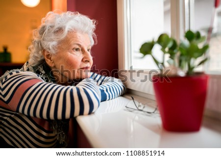 Sad alone senior woman looking through window at home, loneliness concept Royalty-Free Stock Photo #1108851914