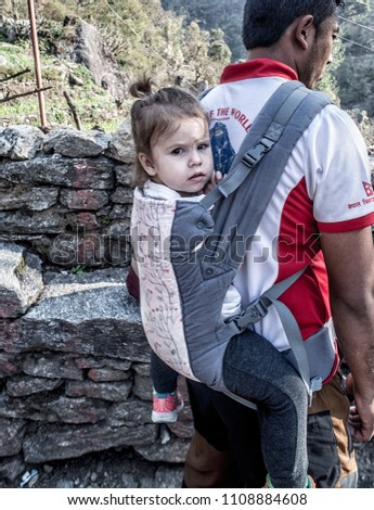 KATHMANDU, NEPAL - April 16, 2018: A man with his toddler child in a baby carrier on the way to Annapurna base camp, Nepal #1108884608