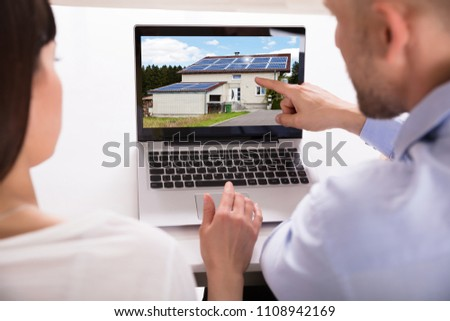 Close-up Of A Couple Looking At House On Laptop Over Desk #1108942169
