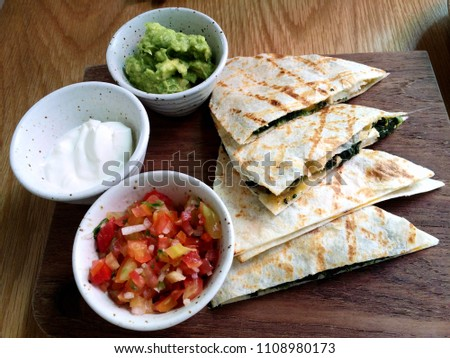 quesadilla salsa appetizer recipe; grilled chicken and spinach with tomatoes, cream, avocado dips #1108980173
