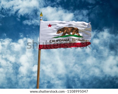 New York, New York /USA - 01.06.2018:California flag USA flag Silk waving flag made transparent fabric of California US state with wooden flagpole gold spear on background blue sky white smoke clouds  #1108995047