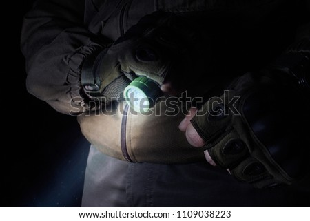 Photo of a male person in brown tactical outfit jacket and gloves using green tactical led flashlight. #1109038223