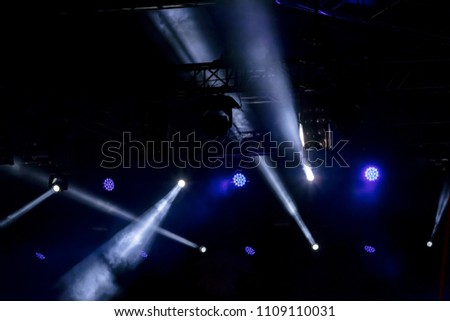 blue lights of projectors and searchlights over dark stage. entertainment industry #1109110031