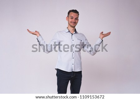 portrait of a cute young brunette man on a white background in different poses with different emotions. He stands directly in front of the camera and shows different emotions #1109153672