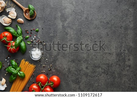 Food background for tasty Italian dishes with tomato. Various cooking ingredients with spaghetti and spoon. Top view with copy space. #1109172617