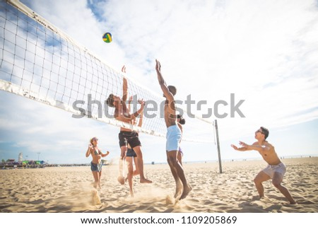 Group of friends playing beach volley - Multi-ethic group of people having fun on the beach #1109205869