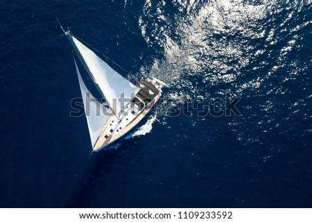 Sailboat while cruising / sailing at opened sea. Yacht with full sails up at the end of windy day. Sailing theme - aerial / drone background. Yachting background design. #1109233592