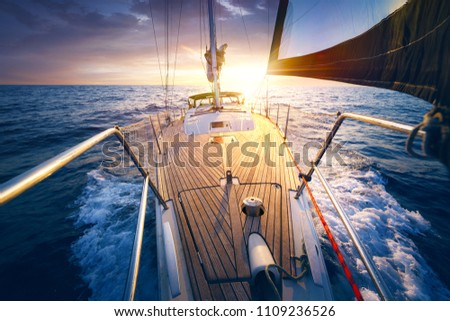 Sunset at the Sailboat deck while cruising / sailing at opened sea. Yacht with full sails up at the end of windy day. Sailing theme - background. #1109236526