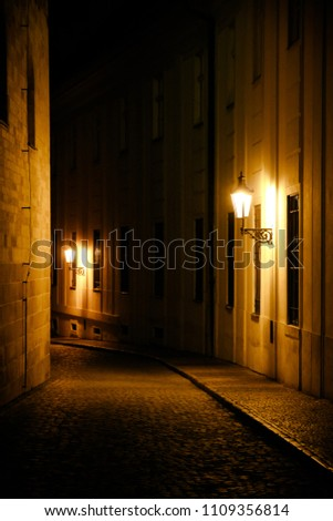 Old lanterns illuminating a dark alleyway medieval street at night in Prague, Czech Republic. Low key photo with brown yellow tones from the lanterns as single light sources against the dark shadows #1109356814