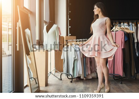 Happy woman trying on new dress in showroom. Fashion and choice concept Royalty-Free Stock Photo #1109359391