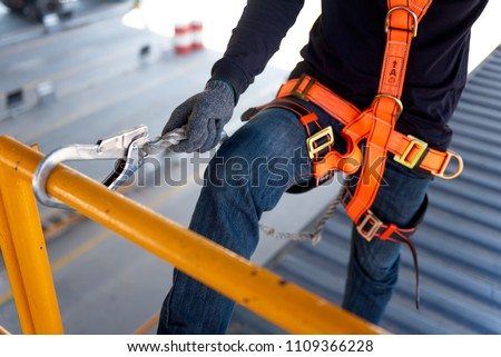 Construction worker use safety harness and safety line working on a new construction site project. #1109366228