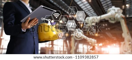 A futuristic architect, Businessman, Engineer manager using tablet with icon network, Industrial robotics, Automation robot arms machine in intelligent construction site. Industry technology concept #1109382857