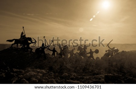 Medieval battle scene with cavalry and infantry. Silhouettes of figures as separate objects, fight between warriors on sunset foggy background. Selective focus #1109436701