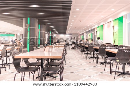 Modern interior of cafeteria or canteen with chairs and tables, eating room in selective focus Royalty-Free Stock Photo #1109442980