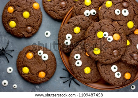 Halloween cookies, chocolate american cookies with candy eyes and chocolate orange and yellow candy dragee, halloween treats for kids