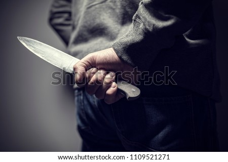 Criminal with knife weapon hidden behind his back #1109521271